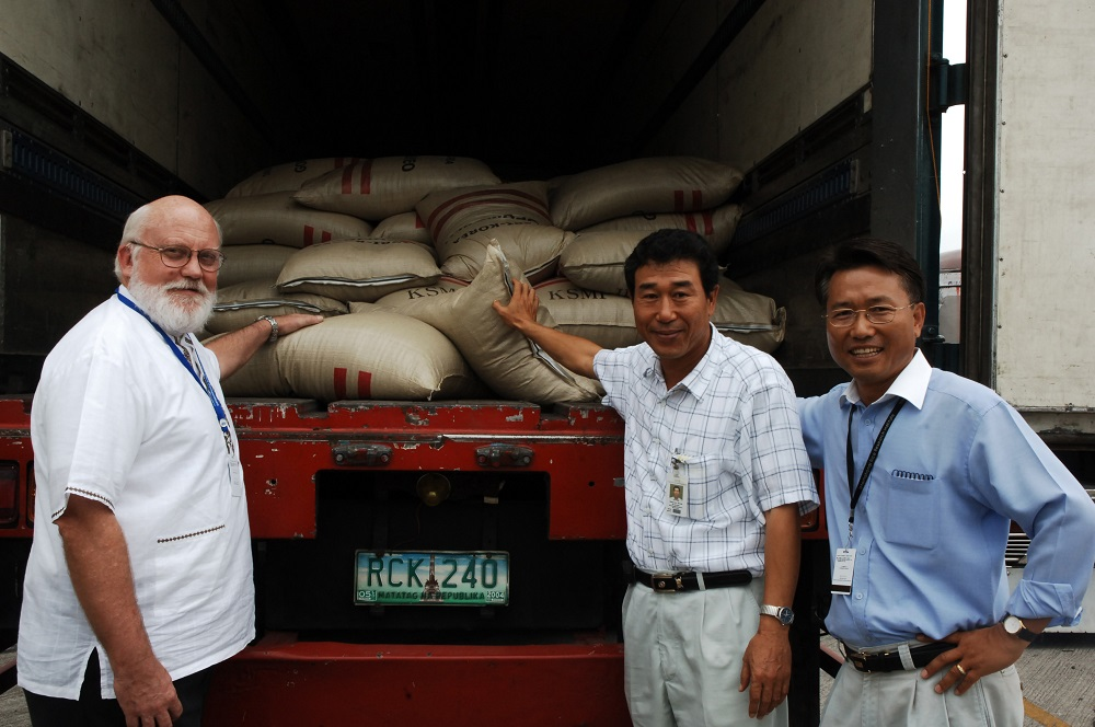 IRRI Senior Scientist Hung-Goo Hwang (center), Visiting Research Fellow Kyu-Seong Lee (right), and IRRI Director General Robert Zeigler inspect one of the seed-laden trucks before its departure. (Photo: Ariel Javellana)