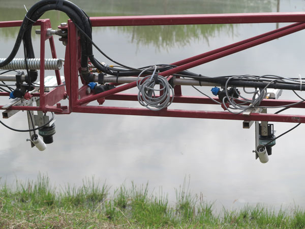 A GPS-guided field canopy sensor system mounted on a spray boom is used to measure some physical traits of rice plants. (Photo: IRRI