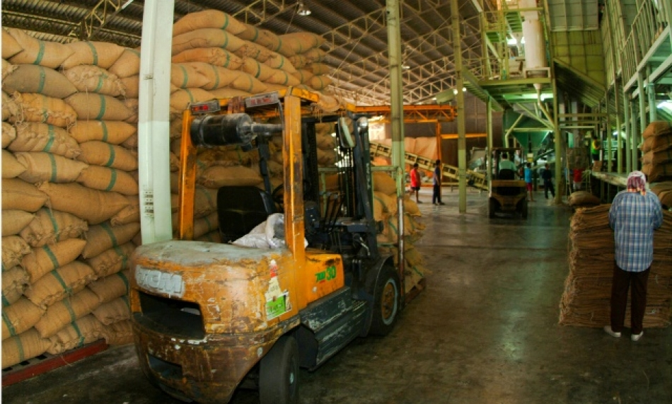 Piles of rice in jute sacks inside a rice mill in Thailand. (Photo: IRRI)