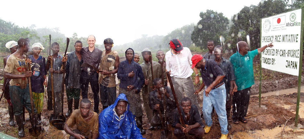 A POURING rainstorm does not stop participants in the Japan-funded Emergency Rice Project in Liberia from posing with Dr. Wopereis (5th from left), Dr. Dobermann (white shirt), and Inoussa Akintayo (far right), African rice coordinator for AfricaRice, (Photo by R. Raman, AfricaRice)