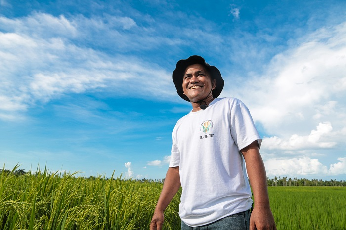 Brilliant blue skies and Green Super Rice bring a smile on Efren Lazarte's face just 24 months after surviving a destructive super typhoon. (Photo: IRRI/Jessieca Narciso)
