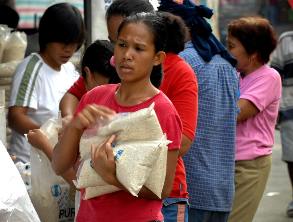 A Filipino woman collects subsidized rice at a market in Quezon City, Manila. High prices have hit the urban poor, many of whom spend a large proportion of their income on rice alone. (Photo: IRRI)