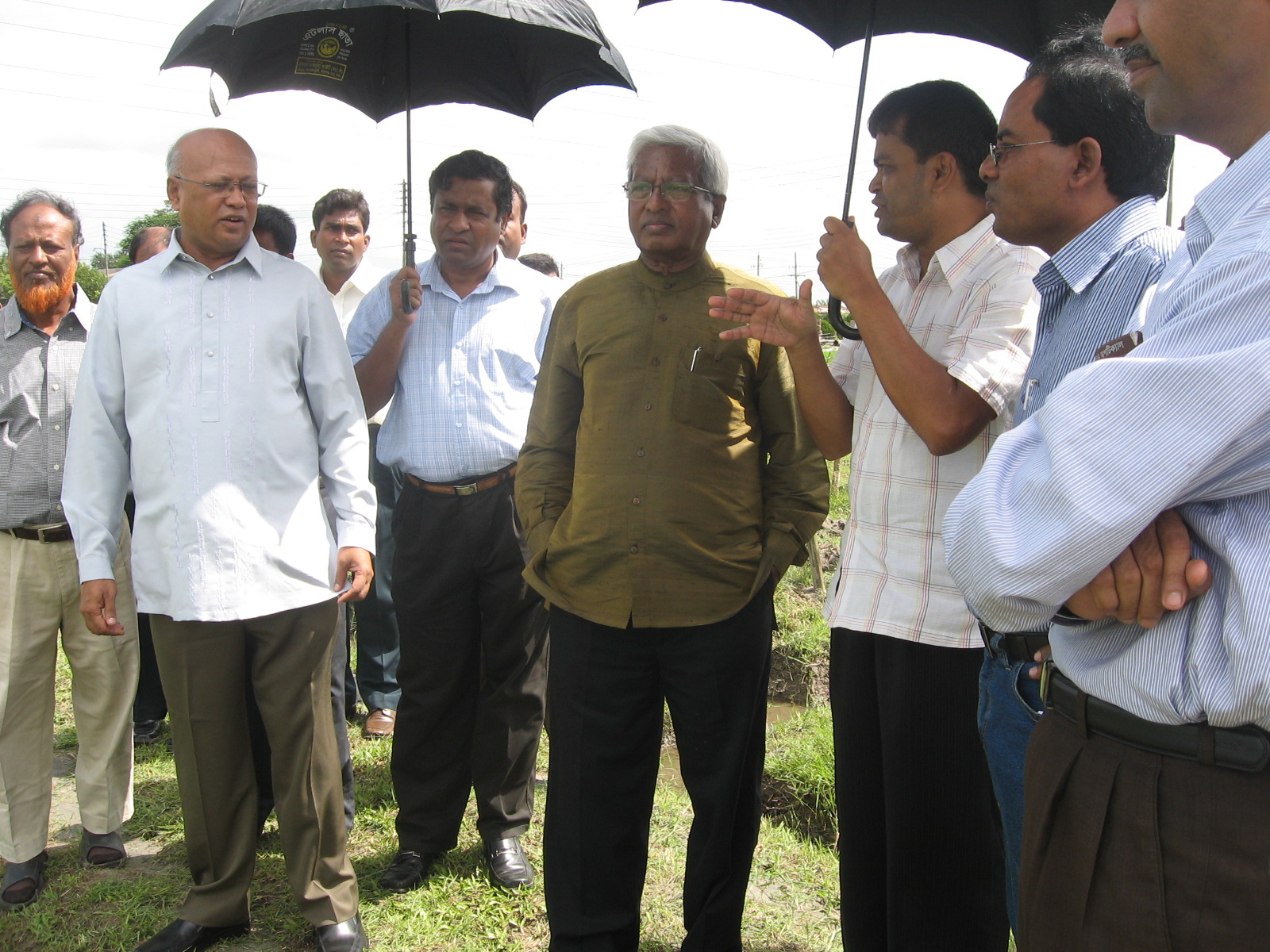 (Foreground, left to right) Dr. Hossain and Sir Abed visit a field in Bangladesh.