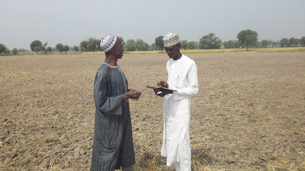 IN NIGERIA, a RiceAdvice service provider (right) collects information to generate customized recommendations on fertilizer options. (Photo by Kokou Ahouanton, AfricaRice.)