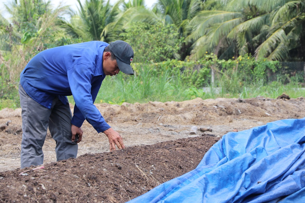 Mr. Thanh, a farmer-partner, examines the output of the rice straw compost turner. (Photo by R. Quilloy)