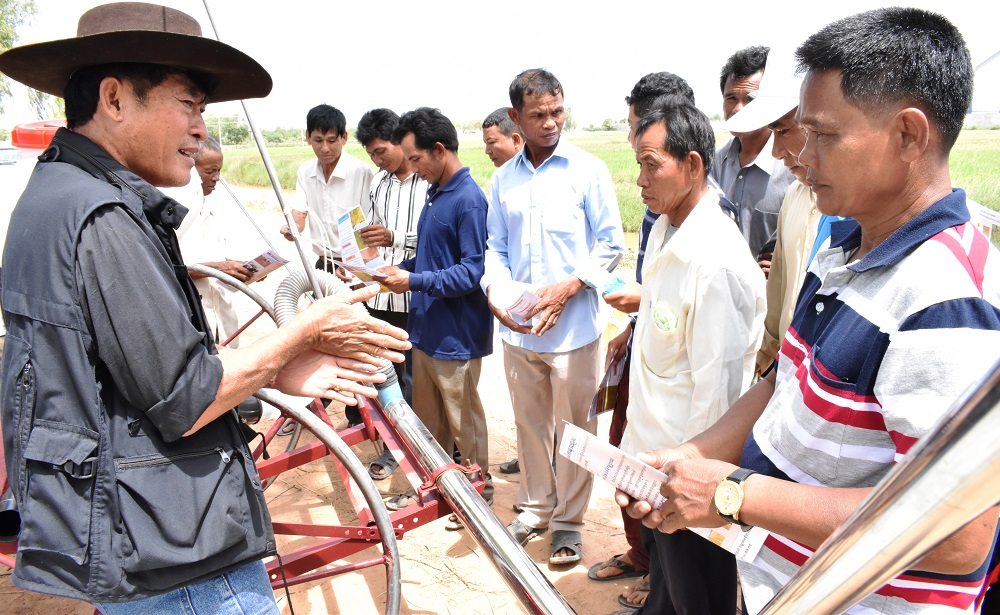 Mr. San, the Cambodia Country Director for Agri-Smart, explains how the Eli Rice Seeder works to farmers at a trade fair. (Photo: IRRI)