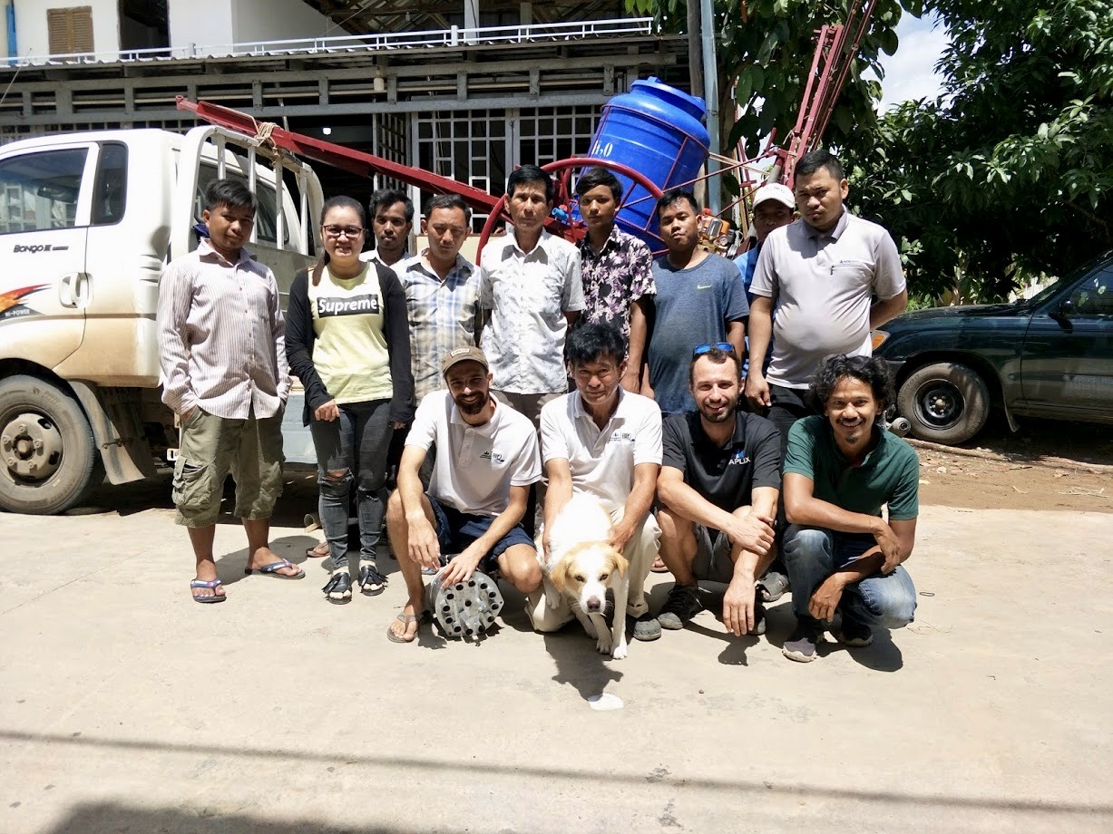 "The ""Village People"" behind the metered seeder: (front row from left to right) Ibrahim FitzGibbon, Bunika San, Tony Morvant, and Veasna Srey, (back row) the Khmer fabricators and staff who made a major contribution to the innovation, and mascot Lovy ,the dog. (Photo: Agri-Smart Cambodia)"