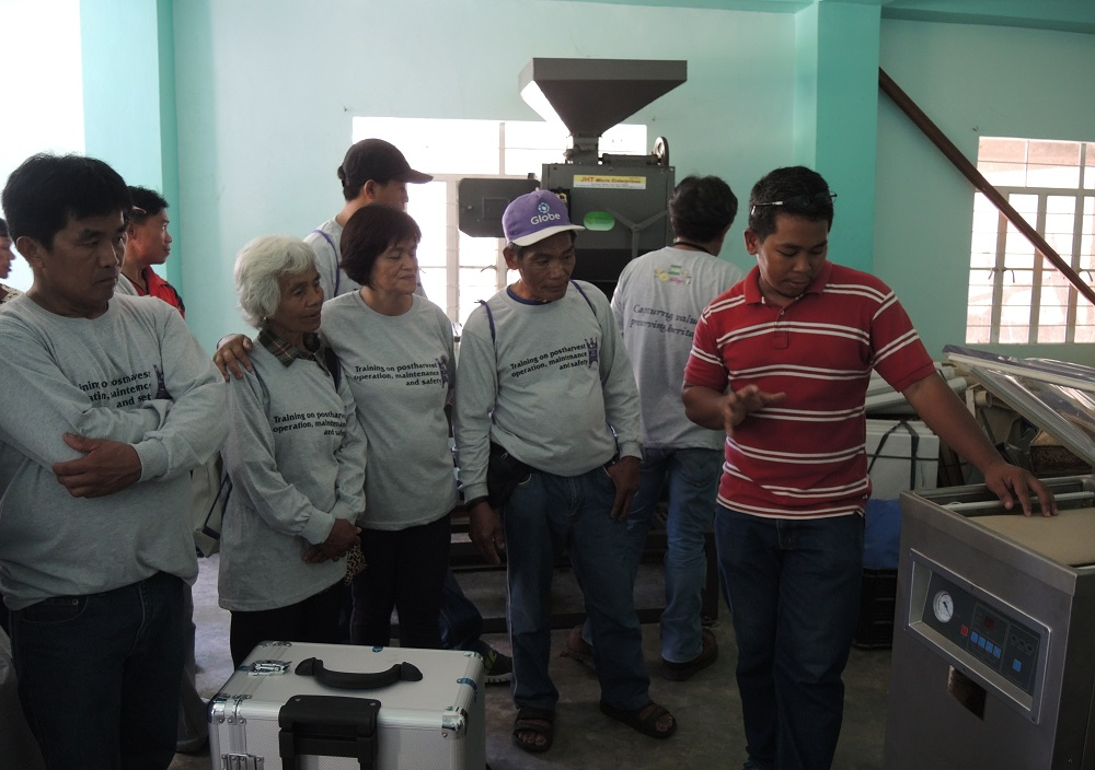 Engr. Sandro (in red) orients members of MPHRFAC on the use of the vacuum sealer to improve the packaging of heirloom rice. (Photo: IRRI)