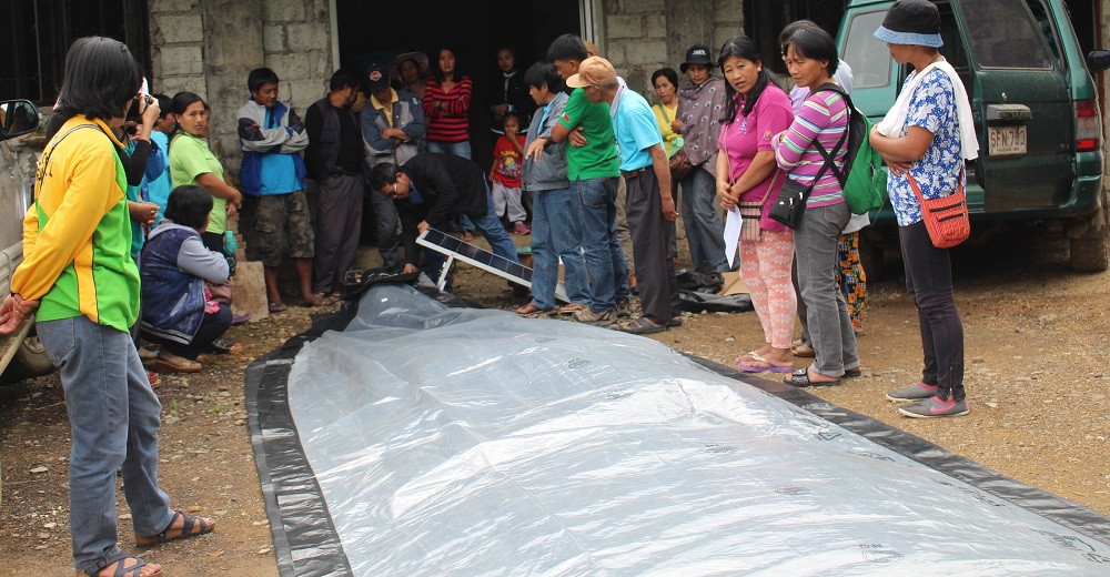 Setting up a solar-powered bubble dryer demo for heirloom rice farmers. The dryer is designed to dry agricultural commodities while protecting them from sudden rain and unpredictable weather. (Photo: IRRI)