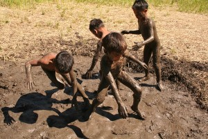 Kids at play along the mudholes of recently harvested rice fields in Bugnay, Kalinga.