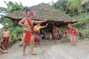 """A family perform a traditional Ifugao thanksgiving dance during the celebration of """"Imbayah"""" Rice Wine Festival in Banaue, Ifugao."""